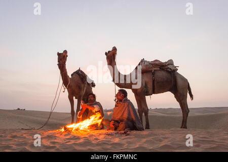Négociant de chameau dans le désert de Thar pendant le lever du soleil. Désert du Thar situé à Jaisalmer, Rajastan, Banque D'Images