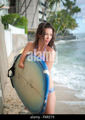Mixed Race amputee transportant de surf