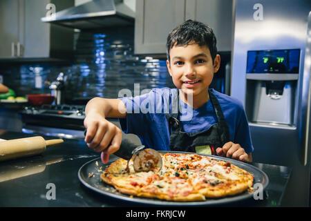 Mixed Race boy slicing pizza dans la cuisine Banque D'Images