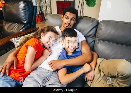 Mixed Race frères et soeur portant sur canapé Banque D'Images