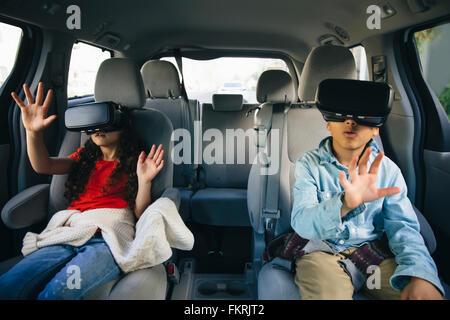 Mixed Race enfants utilisant des lunettes de réalité virtuelle dans... Banque D'Images