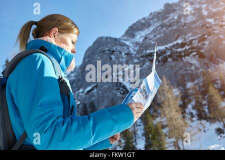 Young woman looking at map en montagnes autrichiennes Banque D'Images