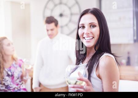 Portrait young woman drinking wine in kitchen Banque D'Images
