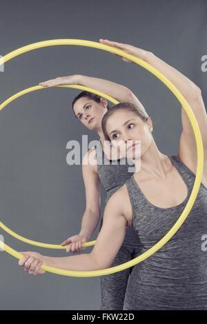 Les jeunes femmes pratiquant avec hula hoop, fond gris Banque D'Images
