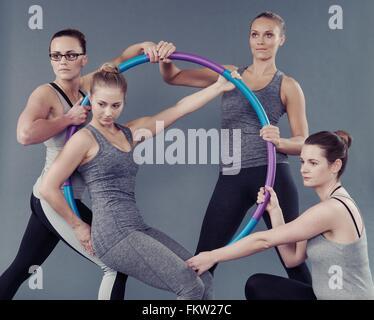 Les jeunes femmes à l'aide de hula hoop, fond gris Banque D'Images