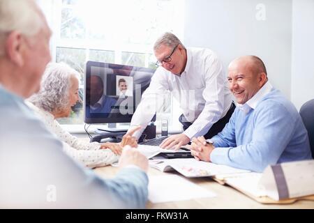 Les hommes d'affaires dans la fice avoir discussion avec senior couple Banque D'Images