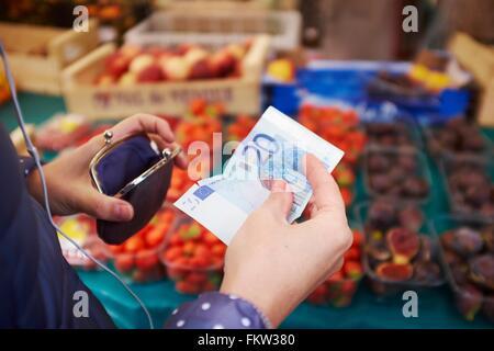 Jeune femme au marché, prendre de l'argent à partir de votre sac à main, mid section Banque D'Images