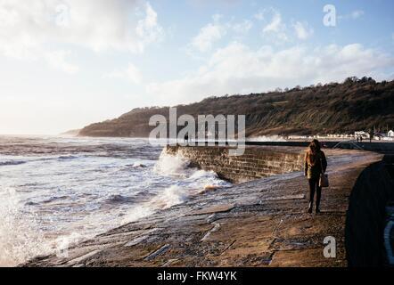 Vue arrière du jeune femme se promener le long de la 'Cobb' mur du port, Lyme Regis, dans le Dorset, Angleterre Banque D'Images