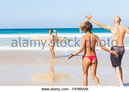 Jeune femme brandissant surfer à des amis, sur la plage, El Cotillo, Fuerteventura, Espagne Banque D'Images