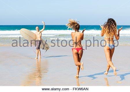Surfer mâle à femelle agitant friends on beach, El Cotillo, Fuerteventura, Espagne Banque D'Images