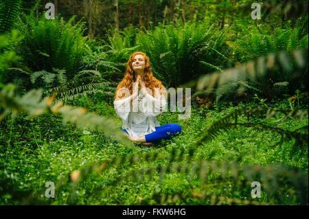 Young woman practicing yoga in lotus position en forêt Banque D'Images