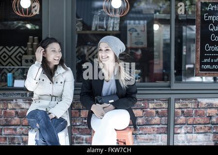 Deux femmes amis assis à l'extérieur ville cafe Banque D'Images