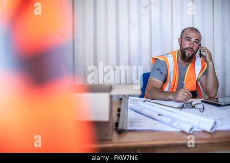 Construction Worker sitting at desk talking on smartphone in chalet transportable Banque D'Images