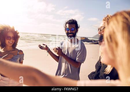 Groupe varié de jeunes se tenant ensemble et parler. Les amis s'amuser sur une journée ensoleillée à la plage. Banque D'Images
