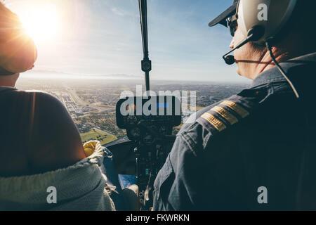 Vue arrière de deux pilotes aux commandes d'un hélicoptère le jour ensoleillé. Gros plan des pilotes assis dans Banque D'Images