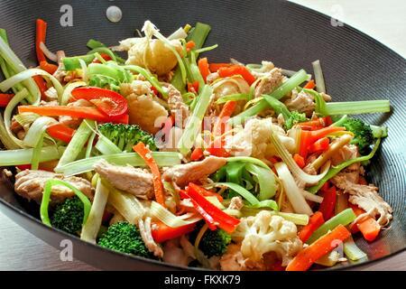 Faire sauter les légumes mélangés avec du poulet dans un wok close up Banque D'Images