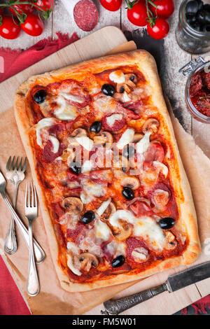 Pizza au pepperoni rectangulaire fait maison sur une table rustique avec des ingrédients. Photographié à partir Banque D'Images
