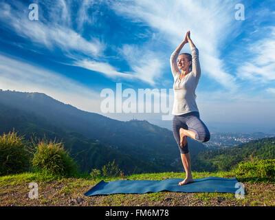 Woman in yoga Vrikshasana posture de l'arbre à l'extérieur Banque D'Images