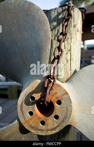 Old Rusty énorme hélice de bateau suspendu à une chaîne lourde sur un quai Banque D'Images