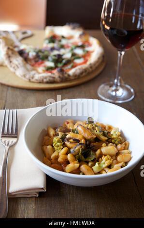 Un bol de haricot blanc, romanesco et les moules soupe avec du vin rouge et une pizza sur la table derrière elle.