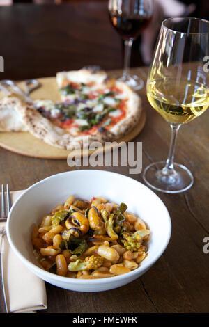 Un bol de haricot blanc, romanesco et les moules au vin blanc soupe et une pizza sur la table derrière elle.