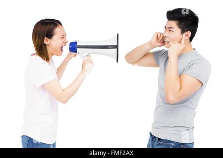 Femme en colère en criant au jeune homme sur haut-parleur à pavillon
