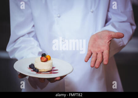 Fier chef holding a plate of cheesecake desert Banque D'Images