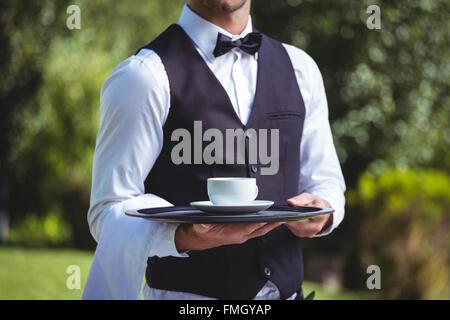 Handsome waiter holding a tray avec tasse de café Banque D'Images