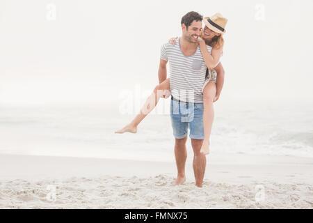 Man giving a piggy retour à la femme sur la plage Banque D'Images