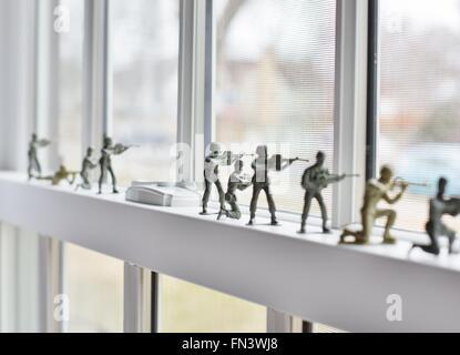 Petits soldats en plastique alignées sur un rebord de fenêtre. Banque D'Images