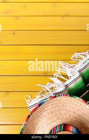 Sombrero mexicain et traditionnel sarape couverture posée sur un plancher de bois de pin peint jaune. L'espace pour copier.