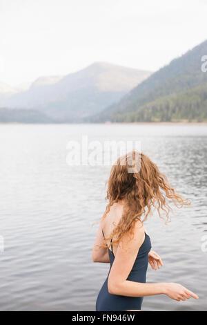 Une femme dans un maillot noir plonger dans un lac calme dans les montagnes. Banque D'Images