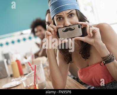 Une femme tenant une photo d'une moustache sur son smart phone juste sous son nez. Banque D'Images