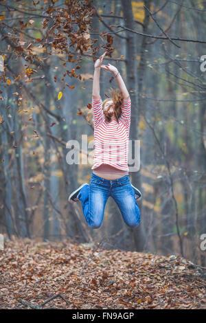 Mid adult woman sautant en l'air dans l'aménagement forestier Banque D'Images