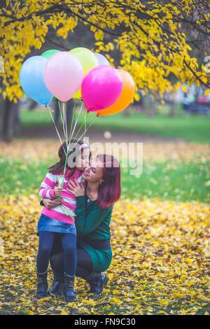 Girl holding balloons embrassant sa mère