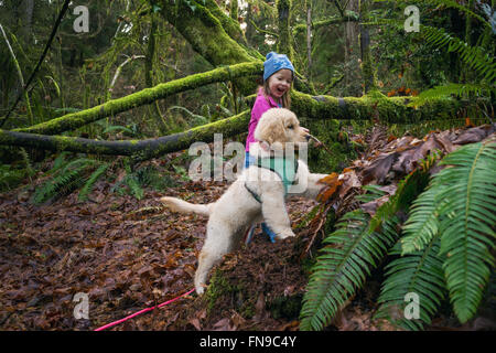 Jeune fille et un chiot Golden Retriever dog creuser dans la forêt Banque D'Images