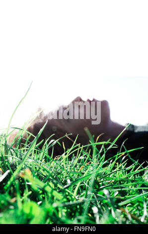 Woman lying on grass Banque D'Images