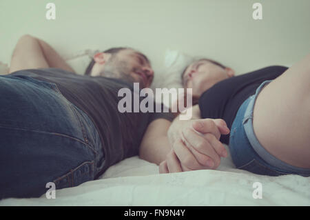 Couple lying on bed holding hands