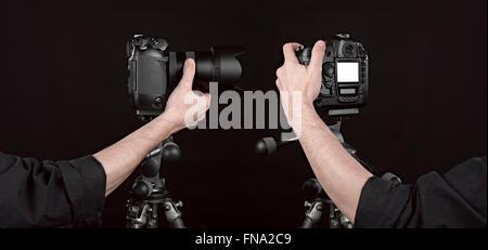 Angle de deux appareil photo numérique noir sur fond noir avec le photographe part poussant le bouton Banque D'Images