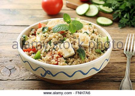 Salade de quinoa avec des légumes frais dans un bol en céramique sur fond de table rustique Banque D'Images