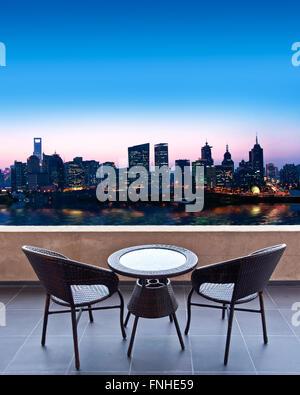 Table et chaises sur la terrasse, vue sur la ville (Shanghai) la nuit Banque D'Images