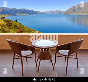 Table et chaises sur la terrasse, vue sur un lac en Nouvelle Zélande Banque D'Images