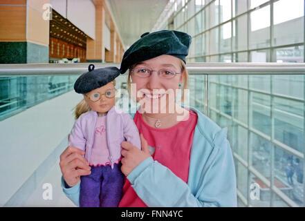 Une petite fille et sa poupée avec des bérets rouges dans l'aéroport (Logan Airport, Boston) heureux d'être sur Banque D'Images
