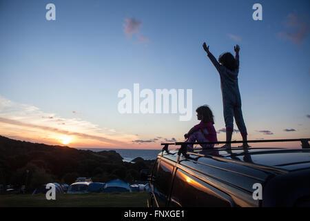 Deux jeunes enfants regarder le coucher du soleil sur un camping. Les souvenirs d'enfance sont faites sur des vacances Banque D'Images
