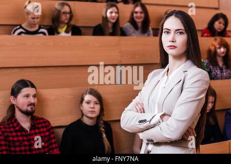Belle enseignante posant en classe avec les élèves Banque D'Images