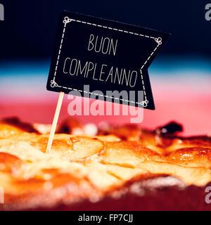 Libre d'une pancarte en forme de drapeau noir avec le texte buon compleanno, joyeux anniversaire en italien topping Banque D'Images
