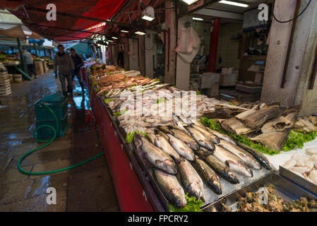 Deux hommes le nettoyage et l'entreposage des étals de marché avec des fruits de mer avant l'ouverture du marché Banque D'Images