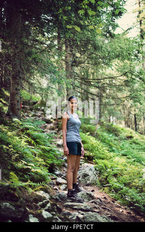 Jolie jeune femme indienne en randonnée dans les montagnes le long d'un sentier forestier à la recherche de l'appareil Banque D'Images
