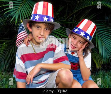 Un jeune frère et sœur dans patriotic stars-et-stripes chapeaux de l'Oncle Sam n'attendent qu'une journée de l'indépendance Banque D'Images