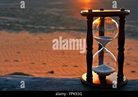 Minuterie de sable sur la plage au coucher du soleil journal patiné glow en arrière-plan. Banque D'Images